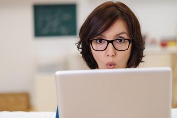 frau schaut auf laptop und macht ein überraschtes gesicht