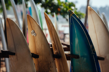 Set of different color surf boards in a stack by ocean. WELIGAMA. Surf boards on sandy Weligama beach in Sri Lanka. On Weligama beach surf is available all year around for beginner and advanced.