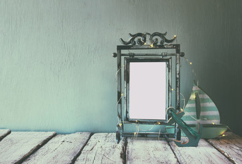 low key image of old victorian steel blue blank frame with fairy garland lights and wooden sailing boat on wooden table. retro filtered image