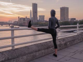 Fitness woman stretching leg on bridge at sunrise