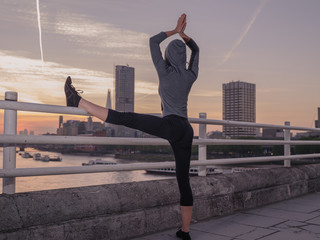 Fitness woman in yoga pose on bridge at sunrise