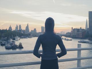Young woman wearing hoodie on bridge in London at sunrise