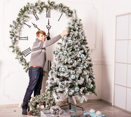 man decorating Christmas tree