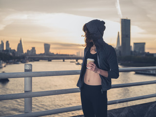 Athletic young woman with cup in London at sunrise