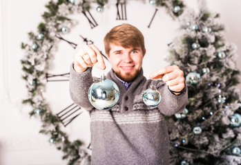 christmas, decoration, holidays and people concept - close up of man  holding christmas ball