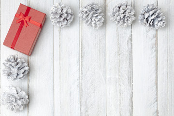 White Christmas border on top left, with red gift box, white wood background