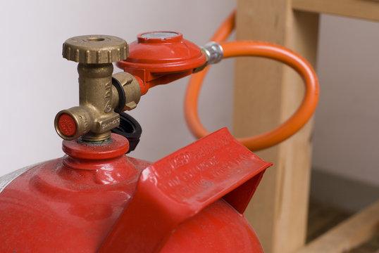 rote Gasflasche mit Propan gefüllt inklusive Druckminderer und Gasschlauch