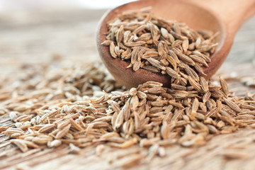 Cumin seeds in a wooden spoon closeup