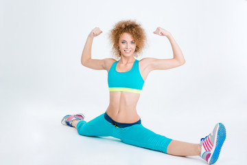 Fitness woman doing twine and showing her biceps
