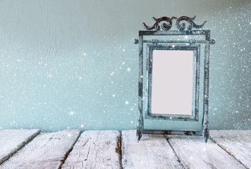 low key image of old victorian steel blue blank frame. vintage filtered image with glitter overlay
