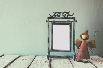 low key image of old victorian steel blue blank frame and cute fairy on wooden table. faded retro filtered image