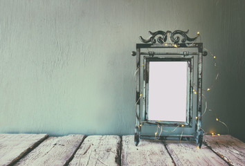 low key image of old victorian steel blue blank frame with fairy garland lights. faded retro filtered image