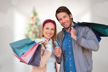 Composite image of smiling couple with shopping bag