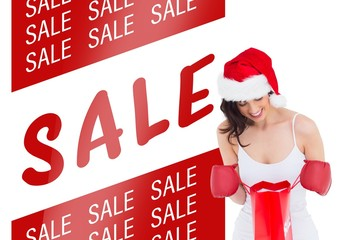 Festive brunette in boxing gloves looking in shopping bag