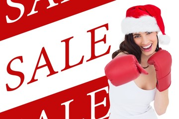 Composite image of festive brunette in boxing gloves punching