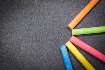 Row of rainbow colored chalk on blackboard