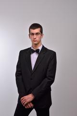 Profile portrait of a fashion young man with glasses in black su