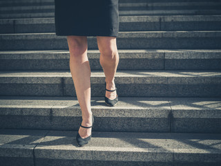 Legs of young businesswoman in city on stairs