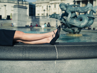 The legs of a young woman by fountain in city
