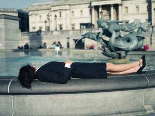 Young businesswoman relaxing by fountain in city