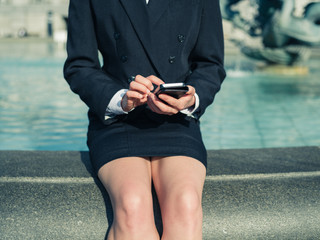 Young businesswoman using smart phone by fountain