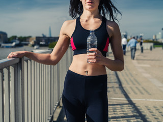 Fit young woman with water bottle in city