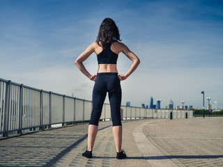 Rear view of athletic young woman in city