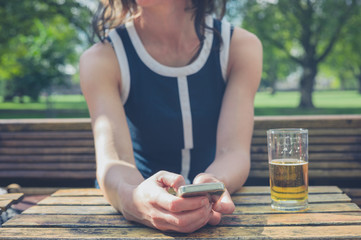 Young woman using smart phone and drinking beer