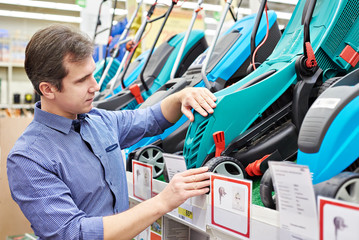 Man choosing lawnmowers in supermarket