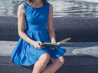 Young woman reading by fountain in the city
