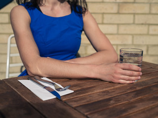 Young woman sitting at table outside restaurant