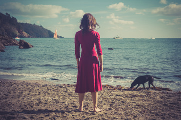 Woman in red dress on beach with dog