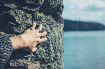 Female hand touching rock by the sea