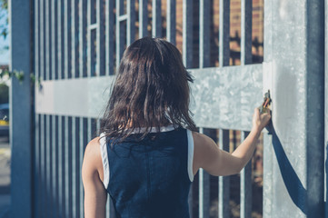 Young woman grabbing padlock by gate