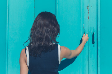 Young woman grabbing blue door