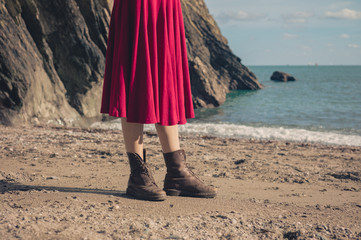 Woman in dress and boots on beach