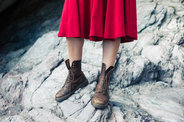 Woman in dress and boots standing on rocks