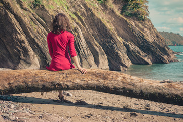 Young woman in red dress relaxing on beach