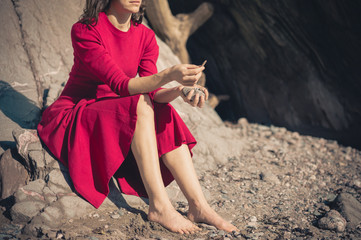 Woman in red dress relaxing by cave on beach