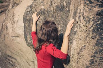 Woman in red dress touching rock wall