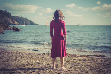 Woman in red dress on a beach