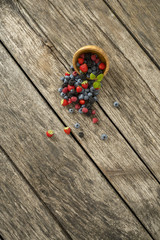 Overhead view of mixed berry fruits scattering out of wooden bow