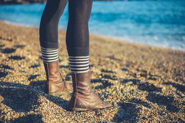 Legs of young woman standing on beach