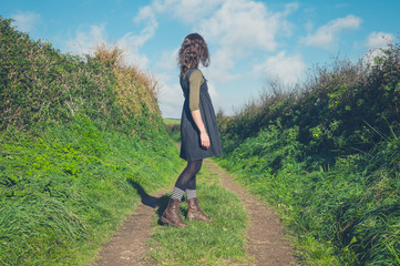 Young woman standing on road in countryside