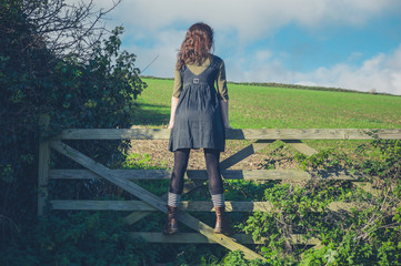Young woman standing on gate in countryside
