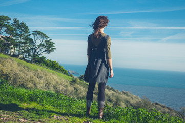 Young woman on hilltop by the sea