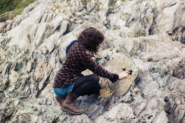 Young woman sitting on rocks and touching stone