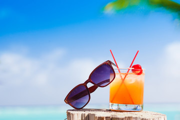 Rum punch cocktail and sunglasses at tropical beach.