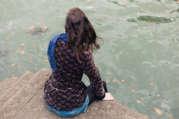 Young woman sitting on concrete pier