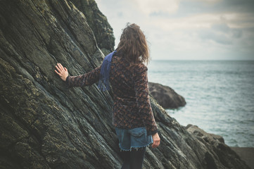 Young woman standing by a rock on the coast